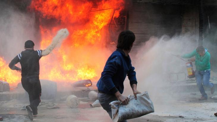 Residents try to extinguish a fire in a gasoline and oil shop in Aleppo's Bustan Al-Qasr neighbourhood October 20, 2013. Witnesses said the fire was caused by a bullet fired by a sniper loyal to Syrian President Bashar al-Assad at the Karaj al-Hajez crossing (photo: Reuters)