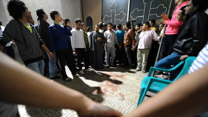 Egyptians gather at a Coptic Christian church in Cairo on 20 October 2013 after gunmen on motorcycles opened fire, killing a woman and wounding several people (photo: AP/Mohsen Nabil)