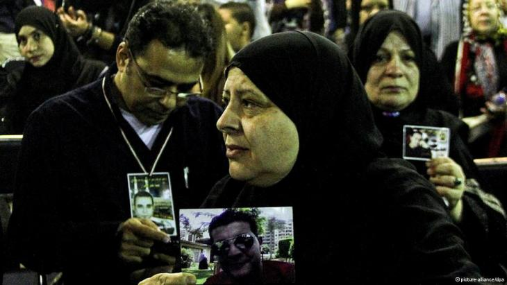 Relatives of the victims hold up pictures of the dead (photo: dpa)