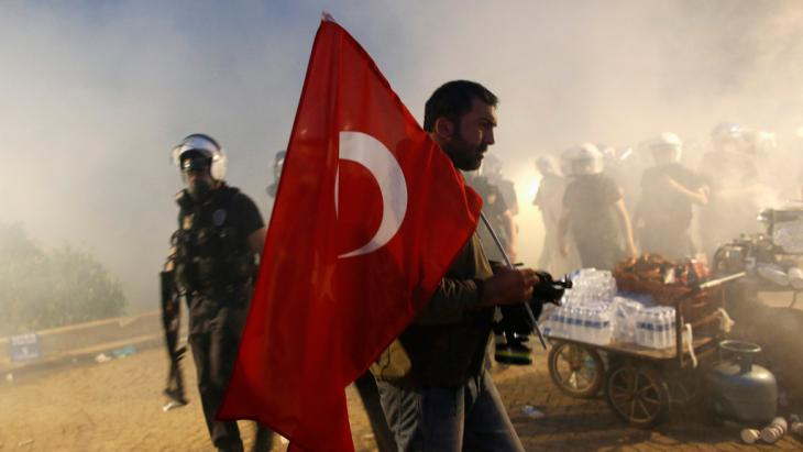 A protester holds a Turkish flag as riot police order them to evacuate Gezi Park in central Istanbul June 15, 2013 (photo: Murad Sezer/Reuters)