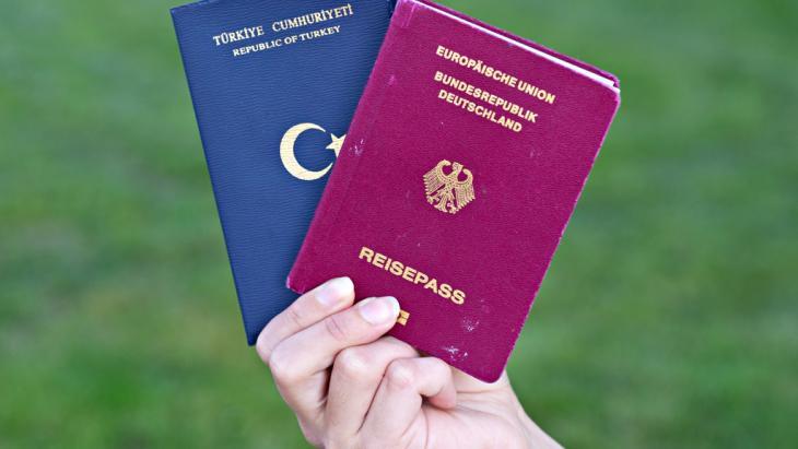 Eine Studentin zeigt  türkischen Pass (l.) und deutschen Reisepass; Foto: picture-alliance/dpa