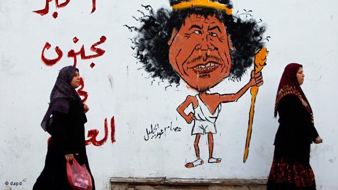 "A mural in Libya depicting former despot of Libya, Muammar Gaddafi. The phrase in Arabic translates as ""The greatest crazyman of the world"" (photo: EPA/Getty Images)"