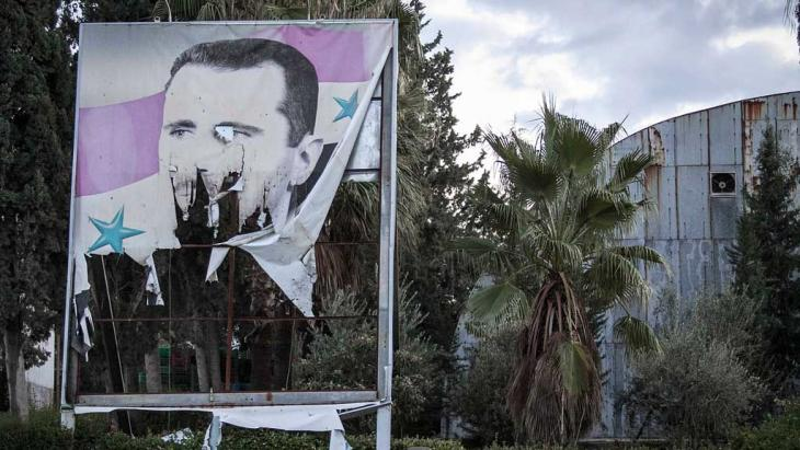 Tattered Assad poster in Aleppo (photo: AP)