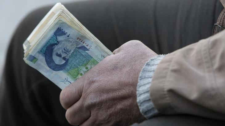 An Iranian man holding Iranian toman banknotes in Tehran (photo: AP)