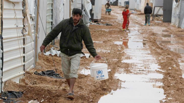 A Syrian refugee walks to collect water after heavy rain at Al Zaatari refugee camp in the Jordanian city of Mafraq (photo: picture alliance/AP Photo)