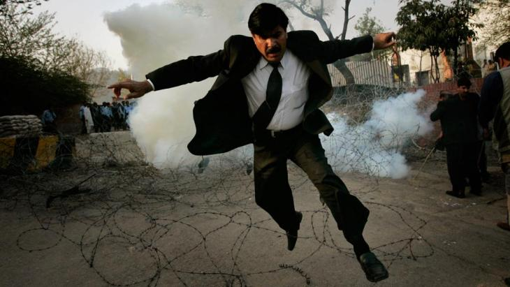 In this March 9, 2008 file photo, a Pakistani lawyer runs away from tear gas fired by police officers outside the residence of the country's deposed chief justice Iftikhar Mahmood Chaudhry during a protest in Islamabad (AP Photo/Emilio Morenatti)