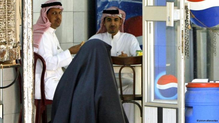 Verschleierte Frau in Jiddah passiert ein Café, in dem Männer sitzen; Foto: picture-alliance/dpa