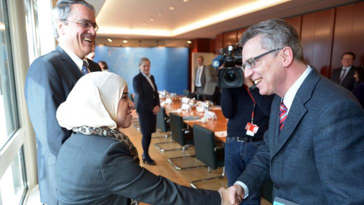 Thomas de Maizière greets a Muslim woman (photo: dpa/picture-alliance)