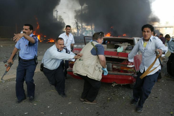 Men dragging a car from the scene of a suicide car bombing of the International Red Cross building in Baghdad, 27 October 2003 (photo: Michael Kamber)