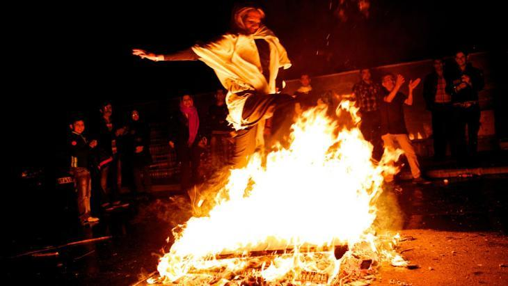 "An Iranian woman jumps over fire during the ""Chaharshanbeh-Soori"" celebratins (photo: Behrouz Mehri/AFP/Getty Images)"