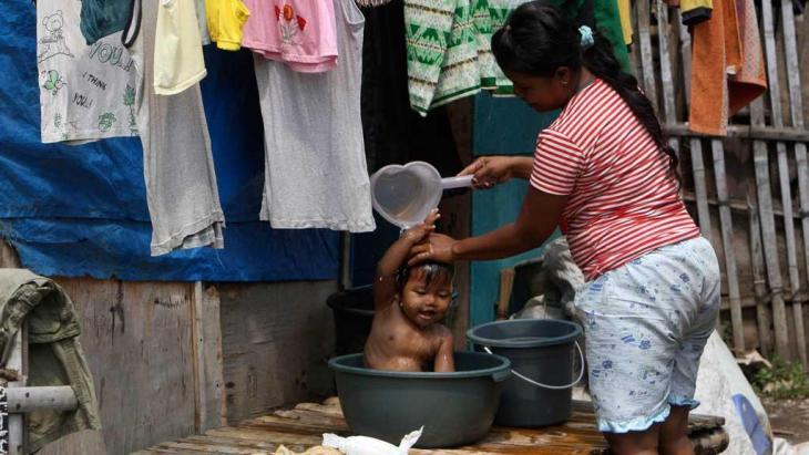 A woman washes her child outside her home in a slum in the Indonesian capital, Jakarta (Photo: AP)