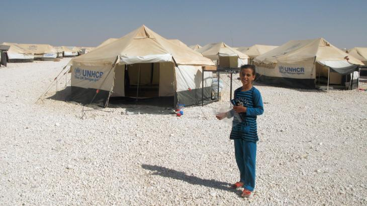 A child stands in front of UNHCR tents in the Zaatari refugee camp in Jordan (photo: picture-alliance/dpa)