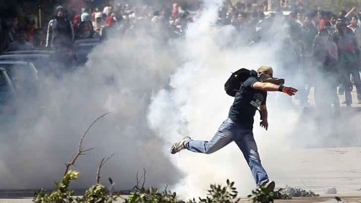 A supporter of the Muslim Brotherhood throws back a tear gas canister launched earlier by riot police during clashes outside Ain Shams University near Egypt's Defence Ministry headquarters in Cairo, 27 March 2014 (photo: Reuters)