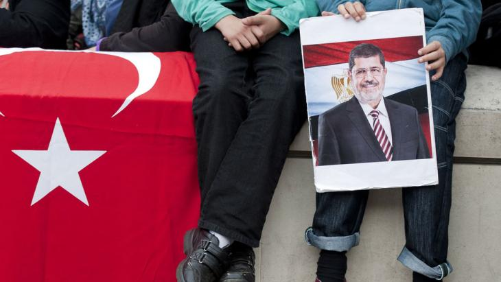 A young demonstrator holds a picture of ousted Egyptian President Mohamed Morsi during a protest in support of the Muslim Brotherhood outside 10 Downing Street, London, on 18 August 2013 (photo: WILL OLIVER/AFP/Getty Images)