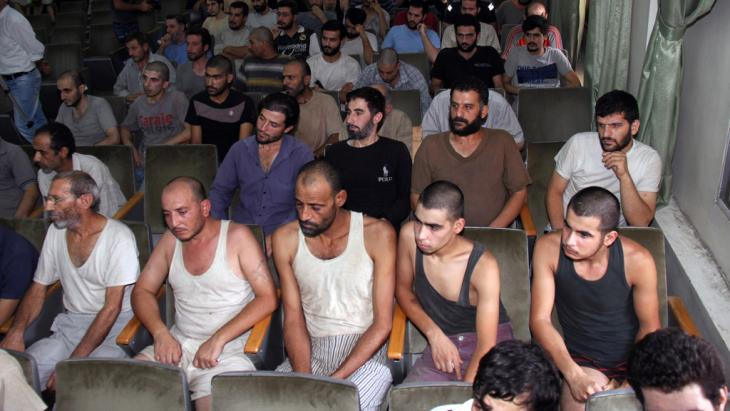 Syrian prisoners sit in a courtroom before their release in Damascus, Syria, on 1 September 2012 (photo: Bassem Tellawi/AP/dapd)