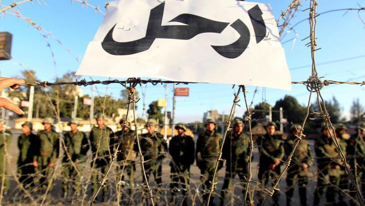 "Army units stand behind barbed wire and a sign that reads ""Get lost!"" outside the presidential palace in Cairo in December 2012 (photo: Reuters)"