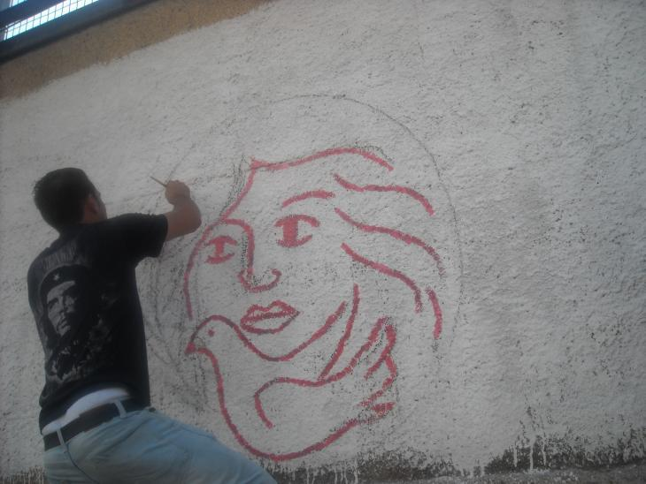 A man paints the logo of the Palestinian Working Woman Society for Development (PWWSD) on a wall (photo: PWWSD)