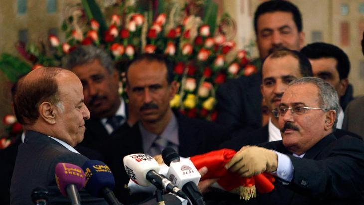Yemeni President Abd-Rabbu Mansour Hadi (left) is handed the Yemeni flag by Ali Abdullah Saleh in Sanaa on 27 February 2012 (photo: Reuters)