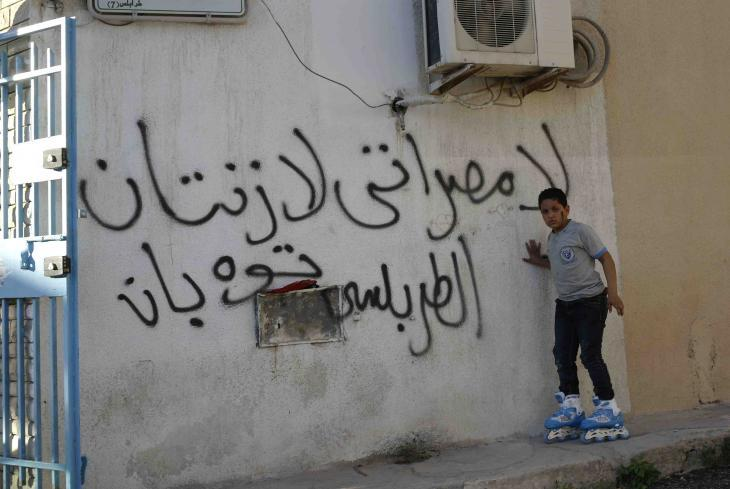 "A boy on roller skates in front of graffiti that reads ""No Misrata, no Zintan"" (photo: Valerie Stocker)"