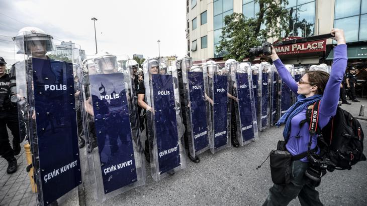 A photographer takes a photo of Turkish riot police officers standing in line as they block access to Taksim square on 31 May 2014 (photo: AFP/Getty Images)