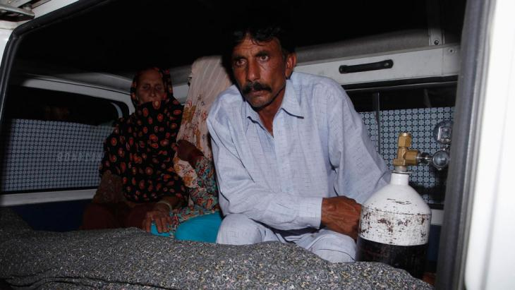 Mohammad Iqbal sits next to his wife Farzana's body in an ambulance outside a morgue in Lahore, Pakistan, 27 May 2014 (photo: Reuters)