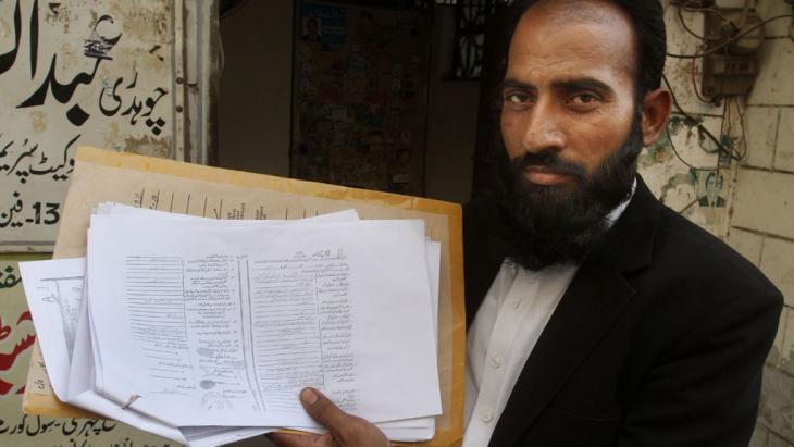 Mustafa Kharal, lawyer of pregnant woman Farzana Parveen, holds up her marriage certificate in Lahore, Pakistan, 28 May 2014 (photo: picture-alliance/AP Photo)