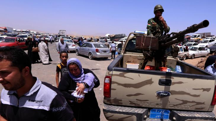 Residents of Mosul and Kurdish Peshmerga fighters at a checkpoint in Aski Kalak (photo: Safin Hamed/AFP/Getty Images)