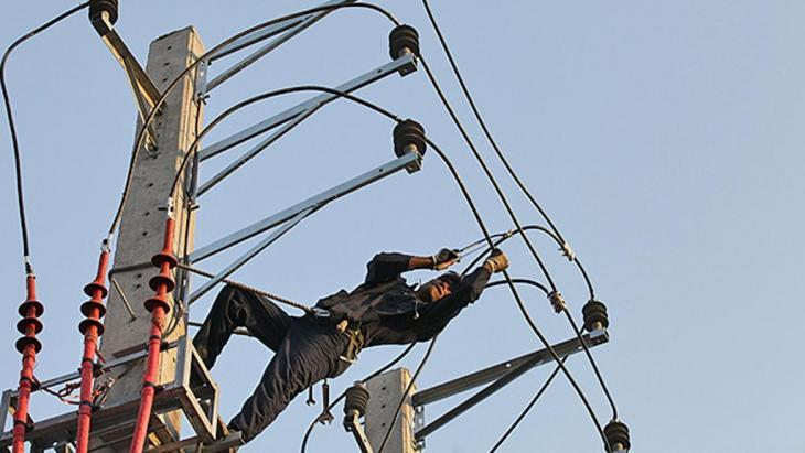 An Afghan worker repairing an electricity pylon in Tehran (photo: INLA)