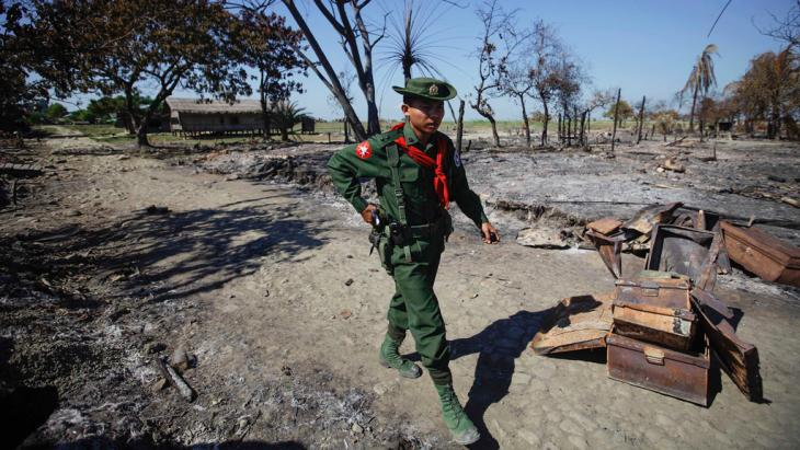A soldier walks amid the rubble of a neighbourhood in Pauktaw township, Myanmar, which was burned in violence in October 2012 (Reuters)