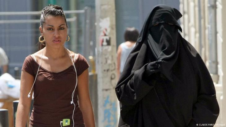 A fully-veiled woman in Paris walking in the street alongside a woman in a T-shirt. Claude Paris/AP/dapd