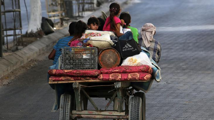 Palestinians flee their homes on a horse-drawn carriage to seek shelter in Gaza City, 13 July 2014. Photo: EPA/MOHAMMED SABER