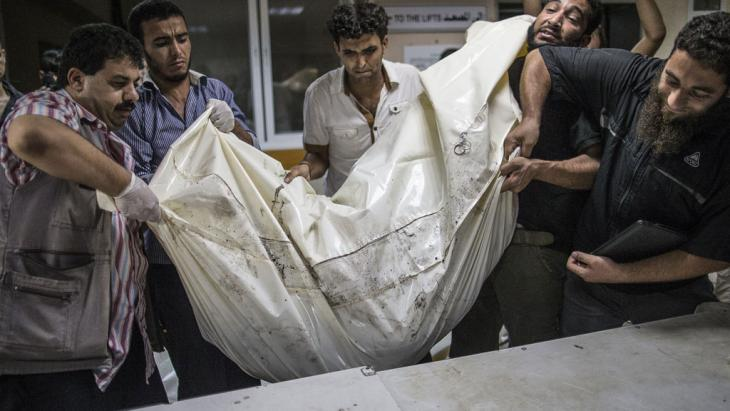 Palestinian volunteers at al-Shifa hospital in Gaza lift a body bag (photo: Marco Longari/AFP/Getty Images)