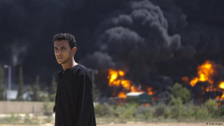 A Palestinian man in front of a burning power plant in Gaza after it was hit by Israeli shelling on 29 July 2014 (photo: Getty Images)