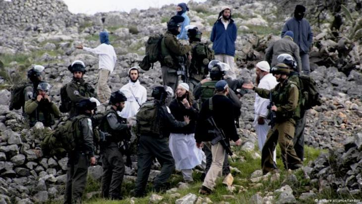 Soldiers breaking up a protest organised by settlers in February 2013 (photo: picture alliance/landov)