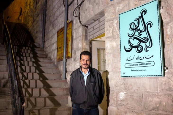 Abu Ahmad in front of his barber shop with its brand new sign (photo: Essa Almasri/Wajha)