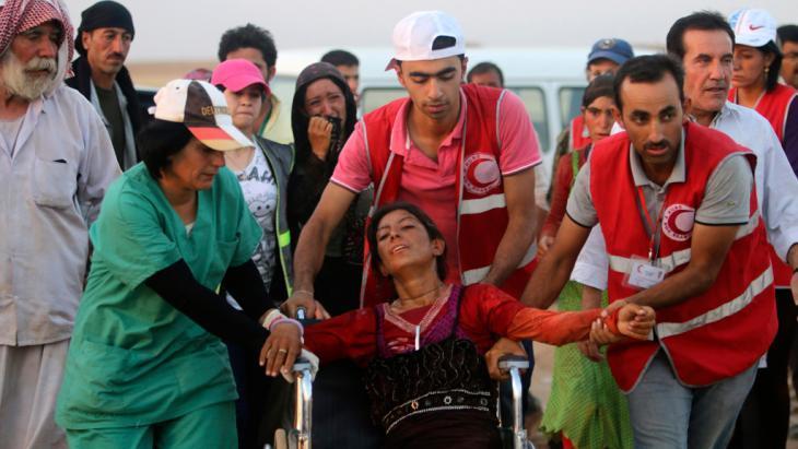 Members of the Kurdish Red Crescent helping a Yazidi woman (photo: Reuters)