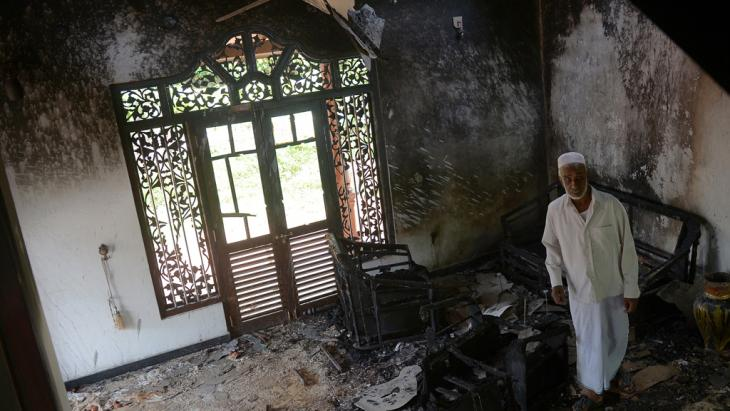 A Sri Lankan resident surveys the damage to a charred Muslim-owned home following clashes between Muslims and an extremist Buddhist group in Alutgama on 17 June 2014 (photo: Lakruwan Wanniarachchi/AFP/Getty Images)
