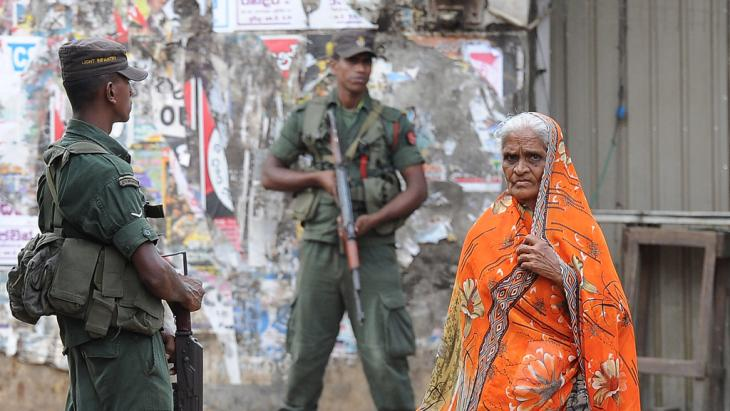 Sri Lankan soldiers stand guard by a roadside following clashes between Muslims and an extremist Buddhist group in the town of Aluthgama, 17 June 2014 (photo: Lakruwan Wanniarachchi/AFP/Getty Images)