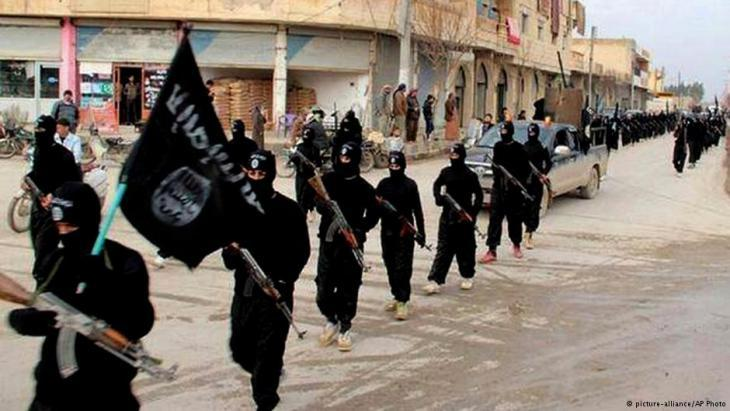 Members of IS terror militias marching down a street in Iraq (photo: picture-alliance/AP)