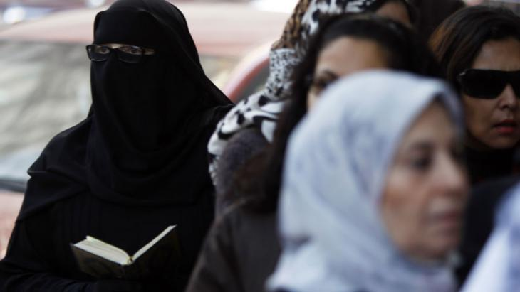 An Egyptian woman wearing a niqab and reading a Koran (photo: Reuters)