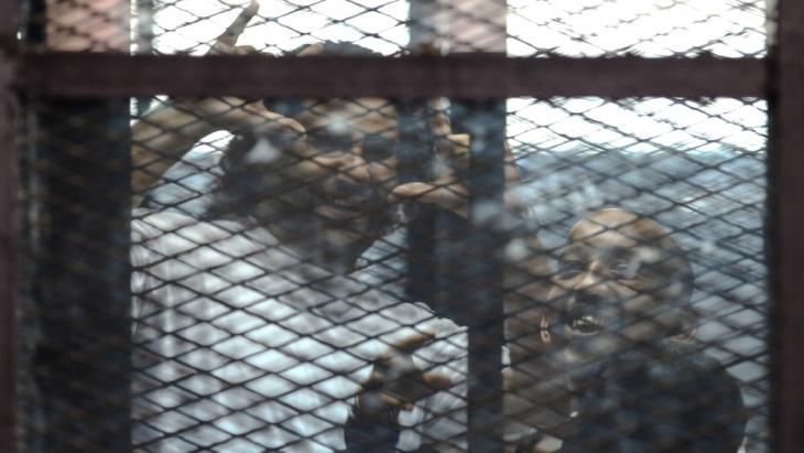 Alaa Abdel-Fattah (left) and Mohamed el-Shahed in a prisoners' cage in a Cairo courtroom (photo: Getty Images/AFP)