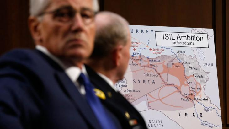 U.S. Secretary of Defense Chuck Hagel (left) and Chairman of the Joint Chiefs of Staff Gen. Martin Dempsey look at a map showing Islamic State ambition, Washington, September 2014 (photo: Reuters/Kevin Lamarque