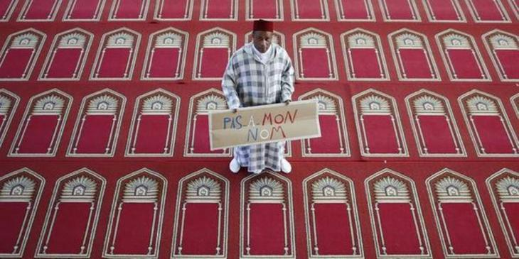 A man holds up a sign that reads #PasEnMonNom (Not in my name) (source: #PasEnMonNom)