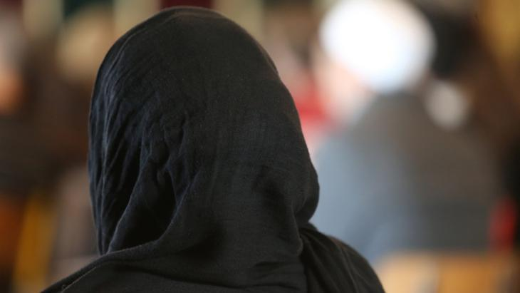 A woman wearing a black headscarf photographed from behind (photo: picture-alliance/Godong)