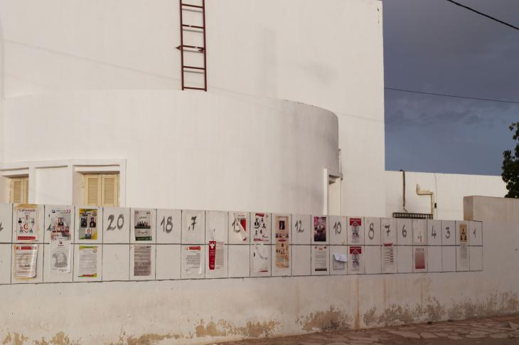 Numbered rectangles painted on a wall in Tunisia, some filled with election posters (photo: Sarah Mersch)