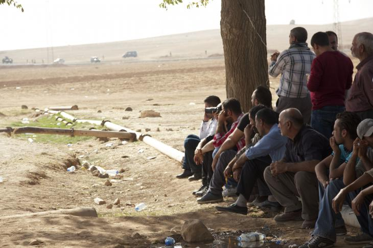 Syrian and Turkish Kurdish fighters wait at the Turkish border for their chance to cross over into Kobani (photo: Kiran Nazish)
