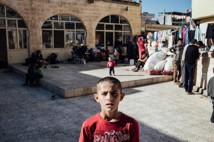 A Syrian refugee child stands outside a mosque used as a refugee camp, Suruc, Turkey, October 2014 (photo: Furkan Temir)