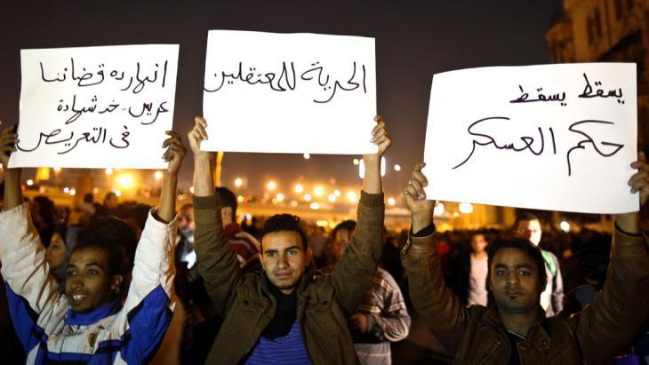 "Demonstrators on Tahrir Square in Cairo holding up placards that read ""down with military law"" and ""freedom for prisoners"" (photo: MOHAMED EL-SHAHED/AFP/Getty Images)"