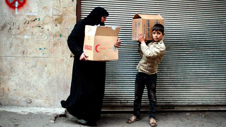 A Syrian woman and her son transporting boxes with food in Aleppo (photo: dpa/picture-alliance)