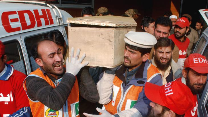 Rescue workers and family members carry the coffin of a student killed during an attack by Taliban gunmen on the Army Public School in Peshawar, 16 December 2014 (photo: Reuters/K. Parvez)